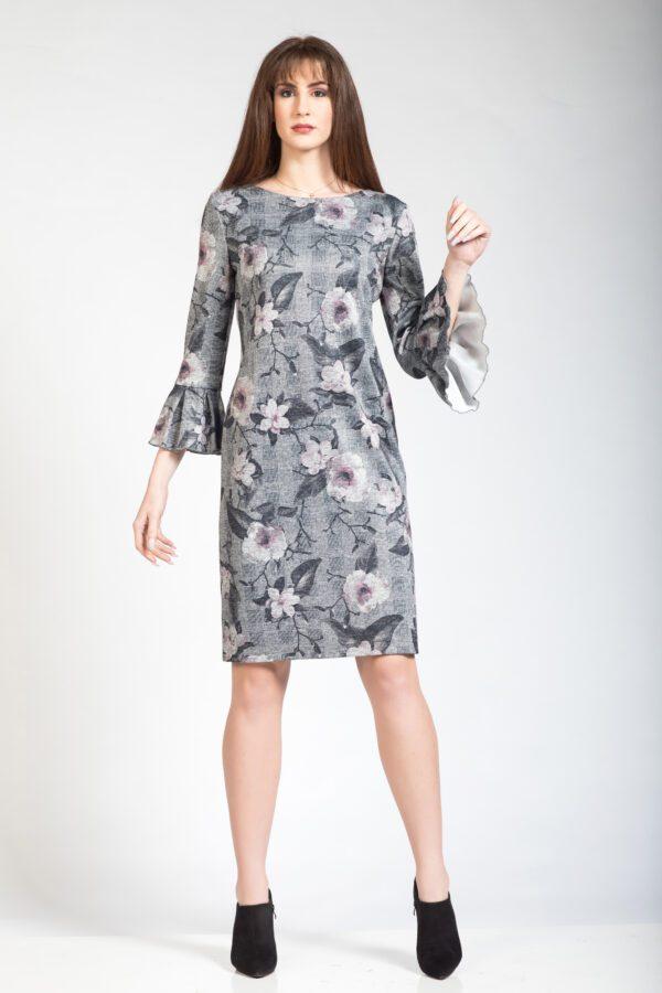 Φόρεμα μακρυμάνικο εμπριμέ με βολάν μανίκι και ελαστική φόδρα. Το φόρεμα κλείνει από πίσω με φερμουάρ.